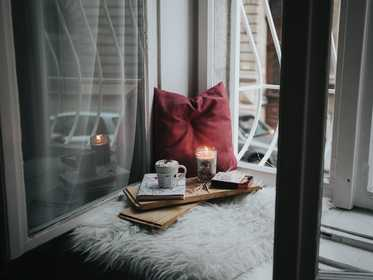 A candle, mug and books in a windowsill