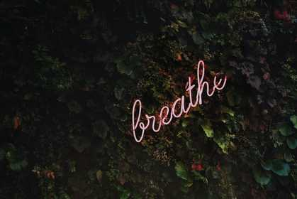 A neon sign saying breathe