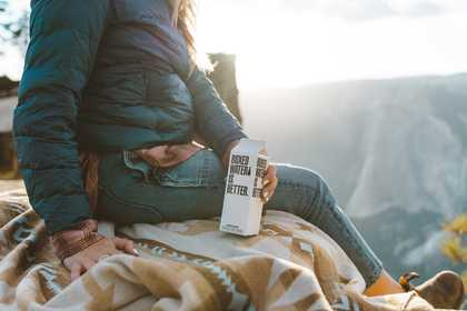 A woman overlooking the mountains with boxed water