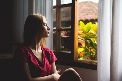 woman meditating by a window