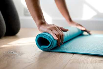 a woman rolling up a yoga mat after exercising